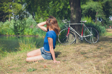 Young woman relaxing by water in the park