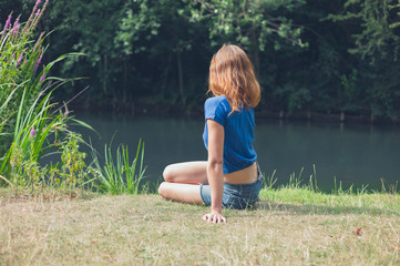 Wall Mural - Young woman relaxing by water in park