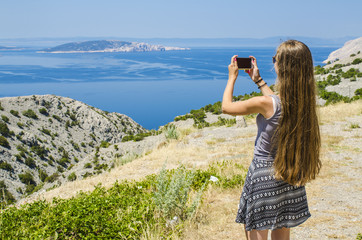 Young attractive girl taking photo of tropical landscape