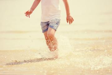 Child running beach shore splashing water, tinted photo