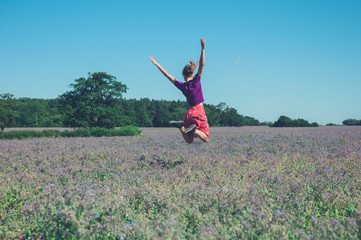 Happy young woman jumping in field of purple flowers