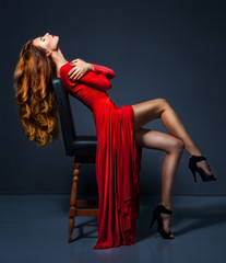 Gorgeous glamour woman in long red dress sitting at the chair. E