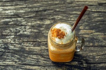 Thai tea and milk frappe on wooden table