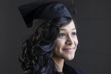 Studio graduation portrait of a young African American woman in her cap and gown, close up