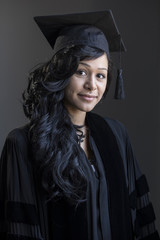 Studio graduation portrait of a young African American woman in her cap and gown