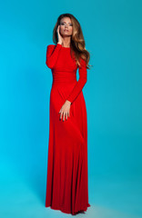 Beautiful young woman in long red dress with healthy curly hair