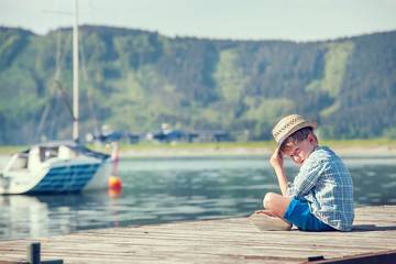 Boy sitting on wooden pier