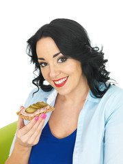 Young Woman Eating a Cracker with German Sausage and Gherkin