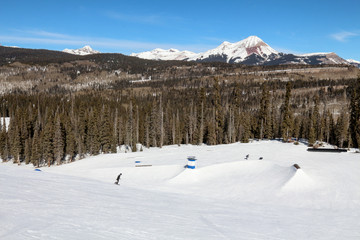 Terrain park with multiple rails and snowboarders