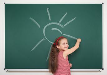 girl drawing sun on school board
