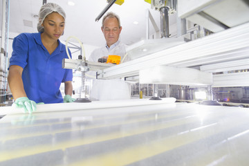 Engineer and Technician worker coating glass for use in production of solar panels