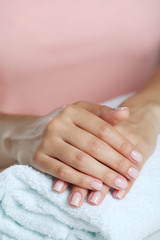 Woman hands with french manicure on towel close-up