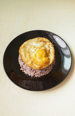 Brown rice with crispy fried egg with space on wood background
