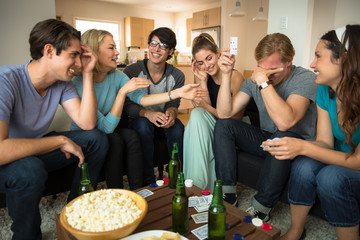 Game night poker playing friends loser embarrassed and winner celebrates at party