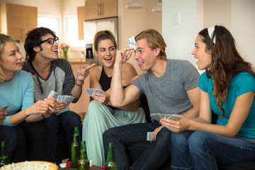 Funny poker player game night group of friends at home laughing