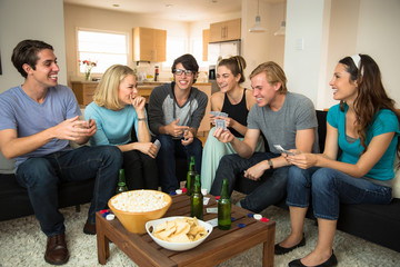 Attractive group of friends at home game night party popcorn beers card playing poker