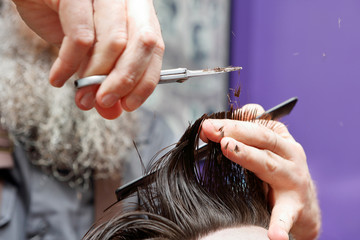 Barber cutting and modeling hair by scissors