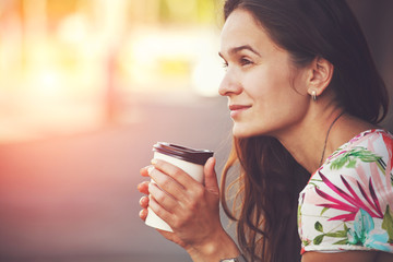 pretty girl sitting in street with morning coffee