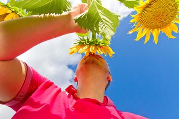 Wall Mural - Mann riecht an einer Sonnenblume