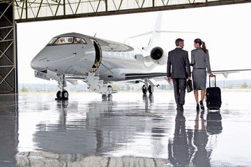 Smiling Businesswoman and Businessman walking toward private jet