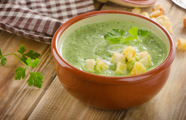 Creamy soup with  croutons on  wooden table.