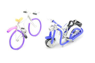 wired purple miniature bicycle and blue scooter place opposite each other isolated white background