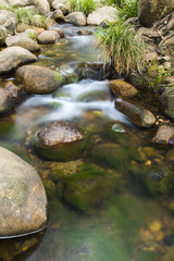 Rocks and flowing water in a creek bed at the base of the mountain Spicers Gap, Queensland, Australia.