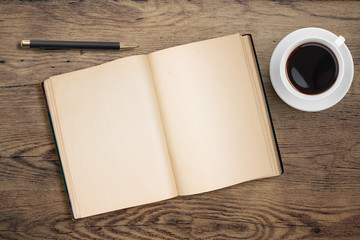 Open diary with pen and coffee cup on old wooden table