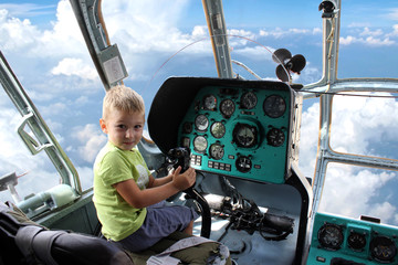 A little boy fly a helicopter.