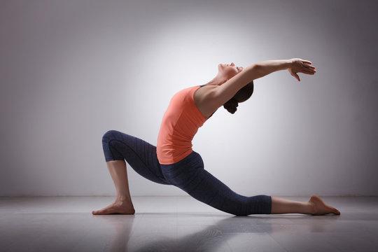 Fit yogini woman practices yoga asana  Anjaneyasana