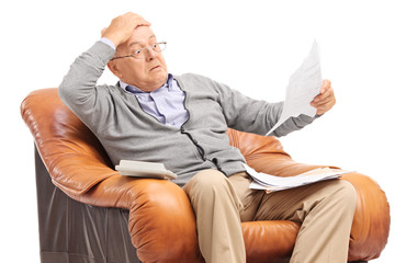 Shocked senior man looking at his bills in disbelief