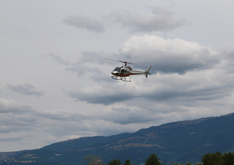 light helicopter flies in the sky and carries tourists