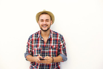 Young man with hat smiling with cell phone