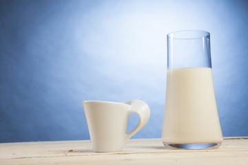 Bicchiere di latte con tazzina su sfondo celeste