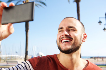 Young man laughing when taking a selfie with mobile phone