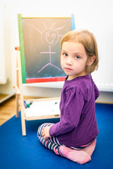 Little child is drawing with color chalk on the chalk board