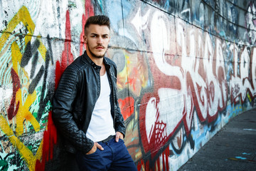 Attractive young man in white shirt and black jacket on graffiti background