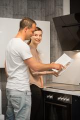 Junges Paar / Frau Mann / in Wohn - Küche mit Kochbuch