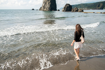波打ち際に立つ女性