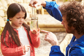 Father And Daughter Looking At Frogspawn In Jar