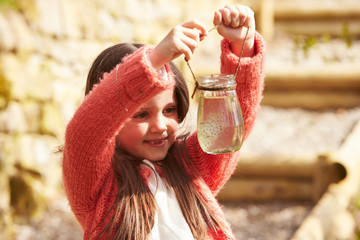 Young Girl Looking At Frogspawn In Jar