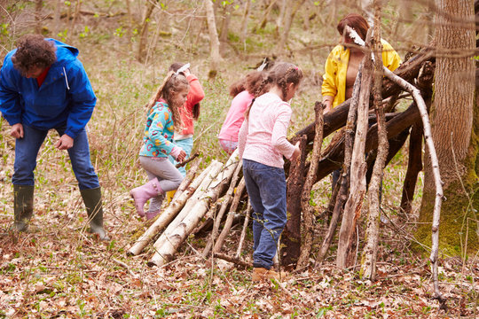 Adults And Children Building Camp At Outdoor Activity Centre