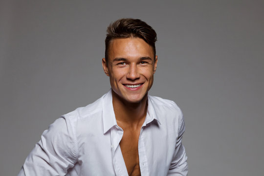 Smiling Young Man In Unbuttoned White Shirt
