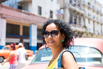 Cuban woman and an old red car in Havana, Cuba