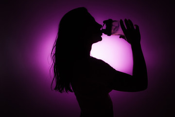 Silhouette of girl drinking a shake.