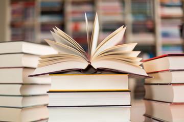 aufgeschlagenes Buch auf Bücherstapel