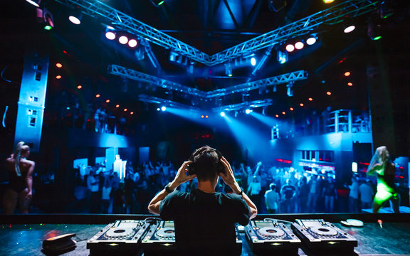 DJ with headphones at night club party