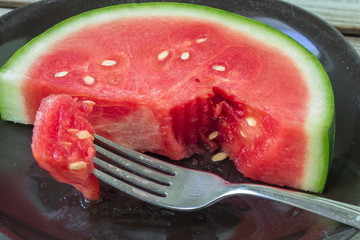 horizontal image of a thick slice of watermelon in a plate with a piece broken off with a fork