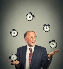 business man in suit juggling multiple alarm clocks