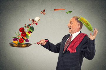 mature happy businessman cooking vegetables with a pan